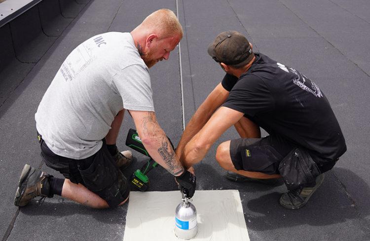 installatie van ankerpunt om leeflijntraject op plat dak te plaatsen